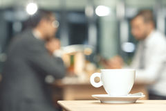 Cup of coffee on a table. With a business partners in the background Stock Photo