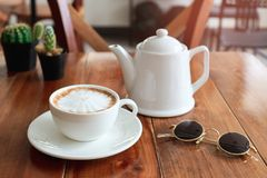 A cup of coffee on table in cafe with glasses stock image