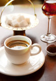 Cup of coffee. On a table. Candy, wineglass and sugar Stock Images