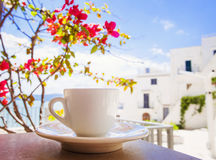 A cup of coffee on table with Italian town at the background. A cup of coffee on table with flowers at the background Royalty Free Stock Photo