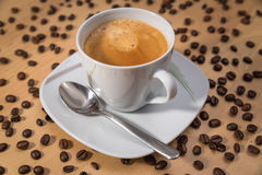 A cup of coffee on a table with many coffee beans Royalty Free Stock Photos