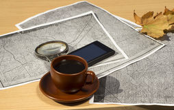 A cup of coffee is on the table next to the old maps and magnifying glass close-up. Royalty Free Stock Photography