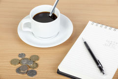 Cup of coffee on table with notepad and coinage Stock Images