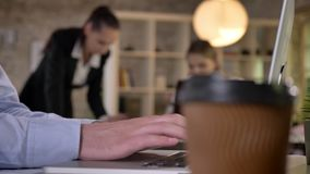 Cup of coffee on table in office, businessman`s hands are typing on laptop, his colleagues are discussing work, blurred. Background, working concept stock video footage