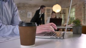 Cup of coffee on table in office, businessman`s hands are typing on laptop, his colleagues are networking with. Technologies, blurred background, working stock footage