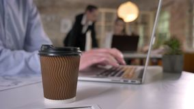 Cup of coffee on table in office, businessman is typing on laptop, his colleagues are networking with technologies. Blurred background, working concept stock video footage