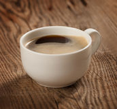 A cup of coffee on the table of the old boards Stock Images