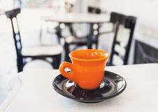 A cup of coffee on table outdoor. A cup of coffee on table with cafe at the background Stock Photography
