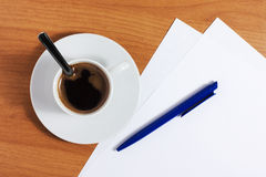 Cup of coffee on table with papers and pen Royalty Free Stock Photography