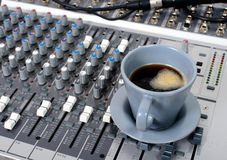 Cup of coffee on a table sound mixer Royalty Free Stock Photography