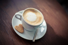 A cup of coffee on the table. White cup of coffee with cream cappuccino in the saucer on the table Stock Photos