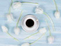 Cup of coffee on a table with white tulips. Royalty Free Stock Photo
