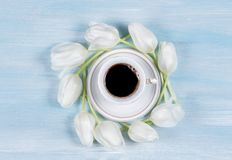 Cup of coffee on a table with white tulips. Top view Royalty Free Stock Images