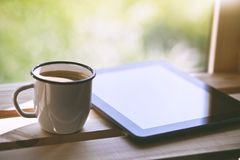 Cup of coffee with tablet computer. Cup of morning coffee with tablet computer stock image