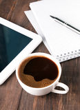 Cup of coffee, tablet and notebook Royalty Free Stock Photo