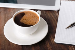 Cup of coffee, tablet and notebook Stock Images