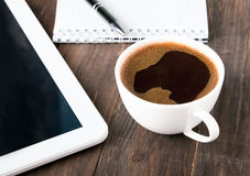 Cup of coffee, tablet and notebook Royalty Free Stock Photos