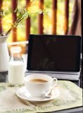 Cup of coffee and tablet on table on a terrace Royalty Free Stock Photography