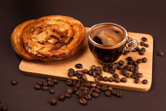Cup of coffee with tasty bun. Cup of coffee with foam, with cookies and coffee beans, lying on the wooden stand, on brown background Royalty Free Stock Photos