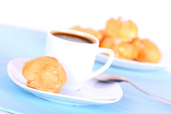 Cup of coffee and tasty cakes on blue mat Royalty Free Stock Image