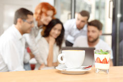 Cup of coffee and tasty dessert on a table. Cup of coffee and tasty dessert  on a table with a friends in the background Royalty Free Stock Image