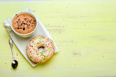 Cup of coffee and tasty donuts with icing and chocolate Royalty Free Stock Photos
