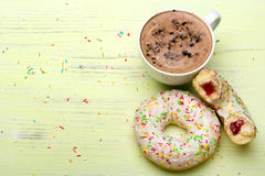 Cup of coffee and tasty donuts with icing and chocolate Royalty Free Stock Image