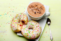 Cup of coffee and tasty donuts with icing and chocolate Stock Images