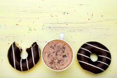 Cup of coffee and tasty donuts with icing and chocolate Stock Photos
