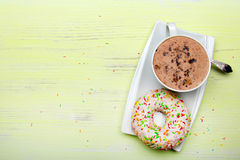Cup of coffee and tasty donuts with icing and chocolate on green wooden background, Stock Image