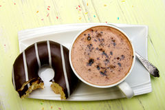 Cup of coffee and tasty donuts with icing and chocolate on green wooden background Stock Photo