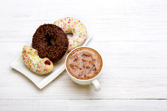 Cup of coffee and tasty donuts with icing and chocolate on white wooden background, Royalty Free Stock Photos