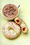 Cup of coffee and tasty donuts with icing and chocolate on wooden background, Royalty Free Stock Photo