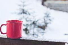 Cup with coffee, tea on the background of the winter landscape. A cup with a hot drink on the background of the winter forest. the table outdoor in the winter royalty free stock photo
