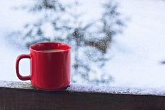 Cup with coffee, tea on the background of the winter landscape. A cup with a hot drink on the background of the winter forest. the table outdoor in the winter stock photography