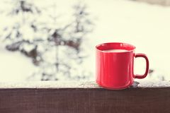 Cup with coffee, tea on the background of the winter landscape. A cup with a hot drink on the background of the winter forest. the table outdoor in the winter royalty free stock image