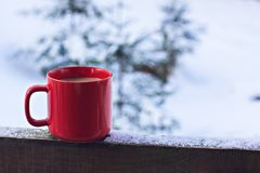 Cup with coffee, tea on the background of the winter landscape. A cup with a hot drink on the background of the winter forest. the table outdoor in the winter stock images