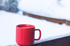 Cup with coffee, tea on the background of the winter landscape. A cup with a hot drink on the background of the winter forest. the table outdoor in the winter stock photo