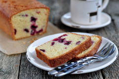 Cup of coffee or tea with a cherry cake on a wooden dinner-table. Cup of coffee or tea with a cherry cake on a wooden dinner table Stock Image