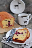 Cup of coffee or tea with a cherry cake on a wooden dinner-table Stock Images