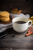 Cup of coffee/tea, cookies, fallen leaves, earphones, and scarf on wooden table. Royalty Free Stock Photography
