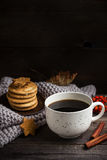 Cup of coffee/tea, cookies, fallen leaves and scarf on wooden table. Royalty Free Stock Image