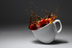 Cup of coffee or tea fell illuminated surface Stock Photos
