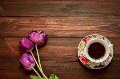A cup of coffee or tea on a saucer stands on a wooden background, purple tulips lie next.  stock photo