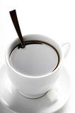 Cup of coffee with teaspoon and sugar slices Royalty Free Stock Images
