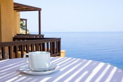 Cup of coffee on terrace with sea view Stock Image