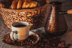 Cup of coffee on textile with beans, dark candy sugar, pots, basket and cake Royalty Free Stock Photos