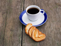 Cup of coffee and three cookies in a row in front, on a wooden t Stock Photos