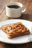 A cup of coffee and toast with almond slices Stock Photos