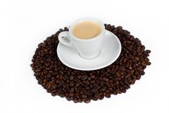 A cup of coffee on top of coffee beans royalty free stock photos